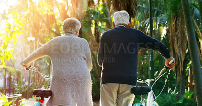 Buy stock photo Rearview shot of a elderly couple pushing their bicycles together outside in a park