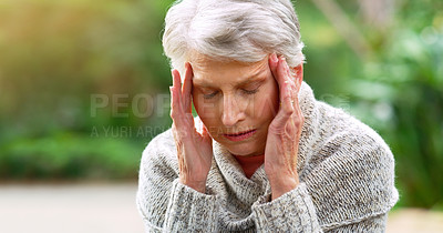 Buy stock photo Cropped shot of a stressed out elderly woman seated on a bench and holding her head in discomfort outside in a park