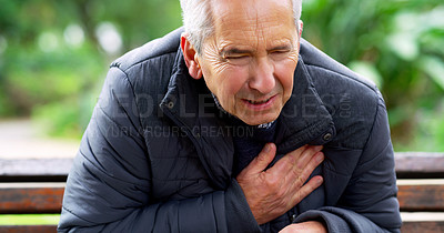 Buy stock photo Cropped shot of a stressed out elderly man seated on a bench and holding his chest in discomfort outside in a park
