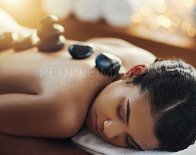 Buy stock photo Shot of a young woman getting a hot stone massage at a spa