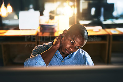 Buy stock photo Cropped shot of a handsome young businessman experiencing tension while using a computer late at work