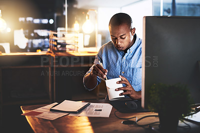 Buy stock photo Cropped shot of a handsome young businessman eating takeout at his desk while working at night in a modern office
