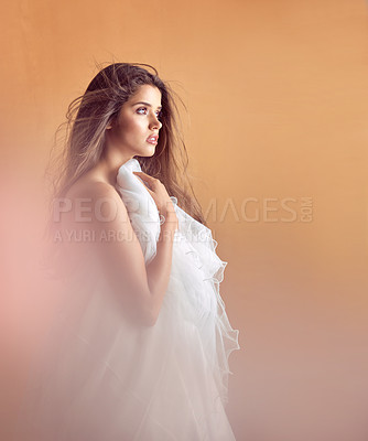 Buy stock photo Studio shot of an attractive young woman posing against a orange background