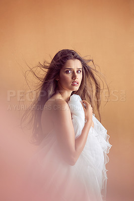 Buy stock photo Studio portrait of an attractive young woman posing against a orange background