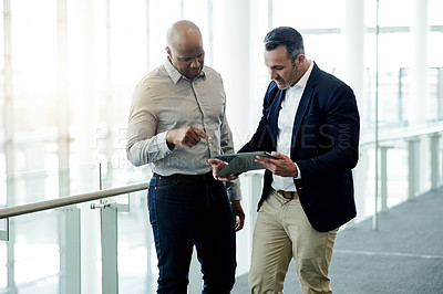 Buy stock photo Cropped shot of two handsome businessmen looking at a tablet in their corporate office