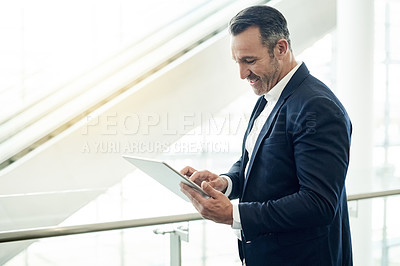 Buy stock photo Cropped shot of a handsome mature businessman using his tablet while standing in the office