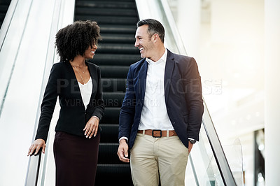 Buy stock photo Cropped shot of two business colleagues coming down an escalator in their corporate office
