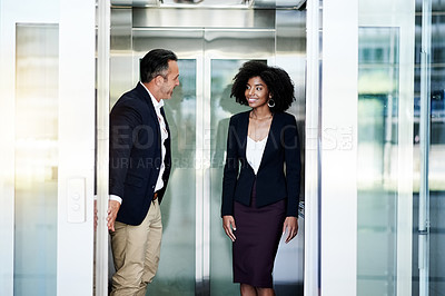 Buy stock photo Cropped shot of a handsome mature businessman holding the elevator door open for a female colleague in their office