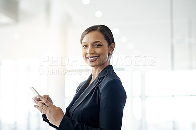 Buy stock photo Portrait of a confident young businesswoman using a cellphone in an office