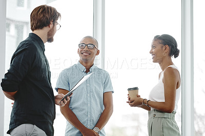 Buy stock photo Shot of three young businesspeople standing and having a discussion in an office