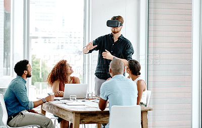 Buy stock photo Shot of a young businessman wearing a VR headset during a meeting with colleagues at work