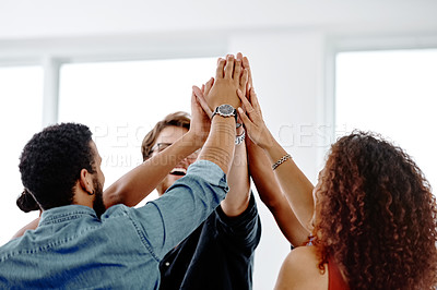 Buy stock photo Shot of a group of cheerful young businesspeople giving each other a high five in their office