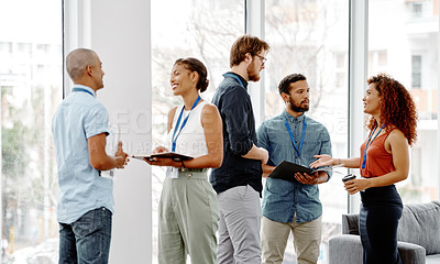 Buy stock photo Shot of a group of young businesspeople standing and having discussions in their office