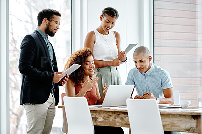 Buy stock photo Shot of a group of young businesspeople using a laptop together in their office
