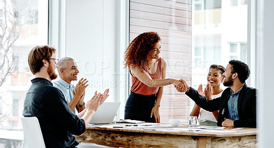 Buy stock photo Shot of two young businesspeople shaking hands during a meeting in an office