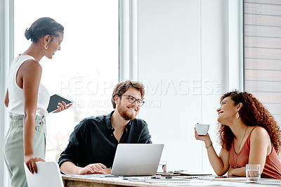 Buy stock photo Shot of three cheerful young businesspeople having a discussion in their office