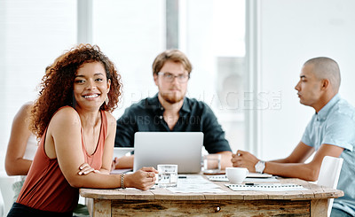 Buy stock photo Portrait of a cheerful young businesswoman sitting around a table with colleagues at work