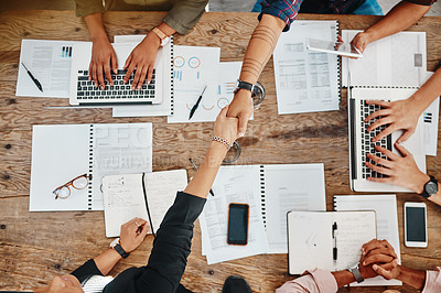 Buy stock photo Shot of colleagues shaking hands during a meeting with colleagues in a modern office