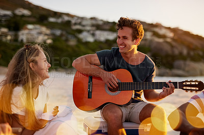 Buy stock photo Shot of a man playing the guitar while sitting on the beach with his girlfriend