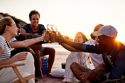 Buy stock photo Shot of a group of friends enjoying drinks on the beach