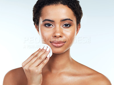 Buy stock photo Portrait of an attractive young woman posing while wiping her face with a cotton pad against a white background