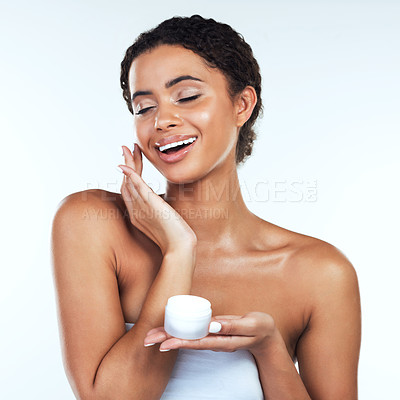 Buy stock photo Studio shot of an attractive young woman posing while applying cream to her face  against a white background
