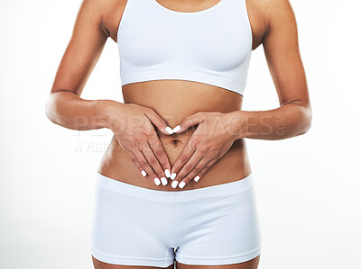 Buy stock photo Studio shot of an unrecognizable woman holding her tummy while standing against a white background