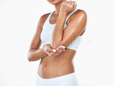 Buy stock photo Studio shot of an unrecognizable woman holding her elbow while standing against a white background