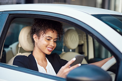 Buy stock photo Cropped shot of an attractive young businesswoman using a smartphone while driving her car