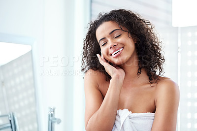 Buy stock photo Shot of a beautiful young woman touching her face while going through her morning routine