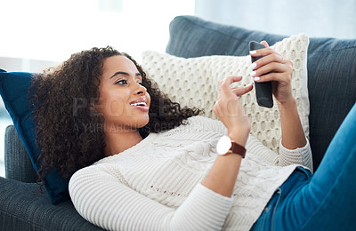 Buy stock photo Shot of a young woman using her cellphone while relaxing at home