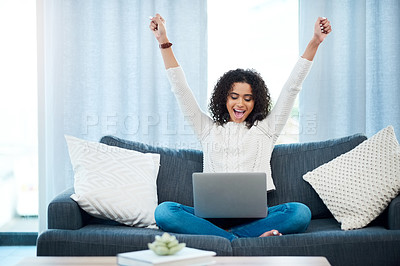 Buy stock photo Shot of a young woman using her laptop while relaxing at home