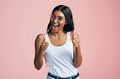 Buy stock photo Studio portrait of a beautiful young woman giving thumbs up against a pink background