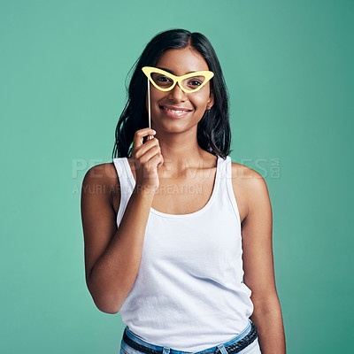 Buy stock photo Studio portrait of a beautiful young woman posing with prop glasses against a green background