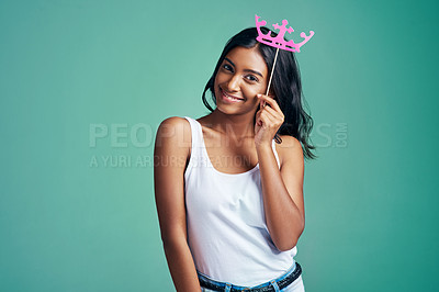 Buy stock photo Studio portrait of a beautiful young woman posing with a prop crown against a green background