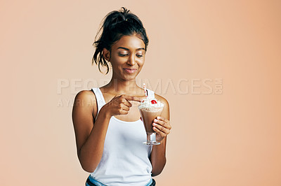 Buy stock photo Studio shot of a beautiful young woman posing with a chocolate milkshake against an orange background