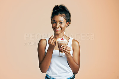 Buy stock photo Studio portrait of a beautiful young woman posing with a chocolate milkshake against an orange background