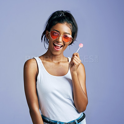 Buy stock photo Studio portrait of a beautiful young woman sucking on a lollipop against a purple background