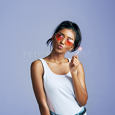Buy stock photo Studio shot of a beautiful young woman sucking on a lollipop against a purple background