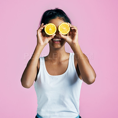 Buy stock photo Studio shot of a beautiful young woman posing with oranges over her eyes against a pink background