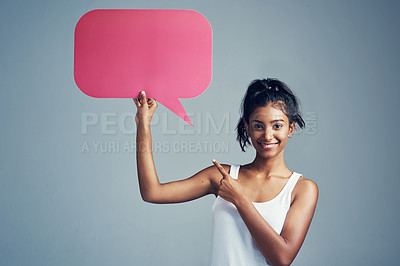 Buy stock photo Studio portrait of a beautiful young woman holding up a blank signboard against a grey background