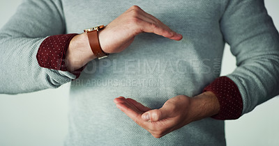 Buy stock photo Studio shot of an unrecognizable man cupping his hands in front of his chest making a symbol while standing against a grey background