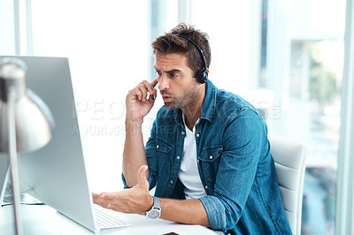 Buy stock photo Shot of a young call centre agent looking upset while working in his office