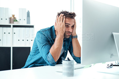 Buy stock photo Shot of a young businessman looking overly stressed out in his office