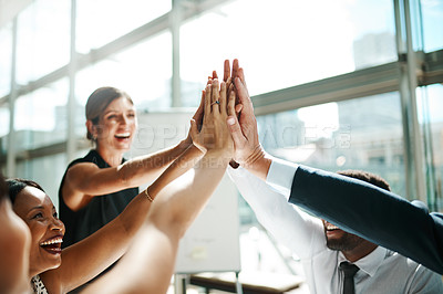 Buy stock photo Shot of a group of businesspeople high fiving while sitting in a meeting