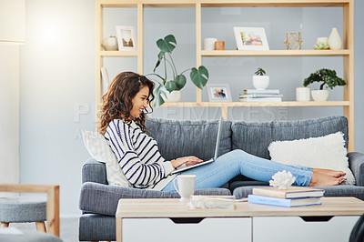 Buy stock photo Full length shot of an attractive young woman using her laptop while relaxing on a couch at home