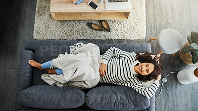 Buy stock photo High angle shot of an attractive young woman relaxing on a couch at home