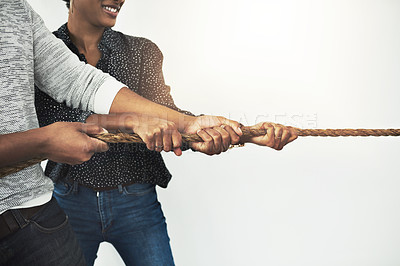 Buy stock photo Cropped shot of corporate businesspeople pulling on a rope during tug of war