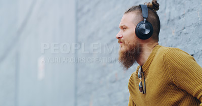 Buy stock photo Shot of a confident young man wearing headphones while listening to music outdoors