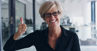 Buy stock photo Portrait of a mature businesswoman showing thumbs up in an office